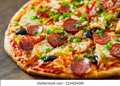 Pizza with Chicken meat, Mozzarella cheese, pepperoni, tomato, olive, salami. Italian pizza on wooden background