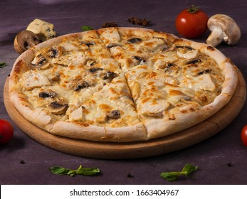 pizza with chicken and mushrooms on a wooden Board