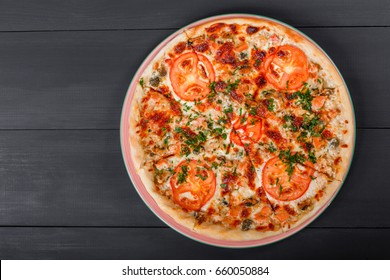Pizza with chicken, tomatoes, mushrooms, greens and cheese on dark wooden background. Homemade pizza. Top view