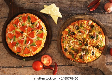 Pizza combo shoot for an offer or deal of Buy one get one free. Vegetarian and non vegetarian Pizza styled for this perfect shot with elements like tomato, cheese, chilli, onion on a wooden background