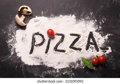 Pizza concept. Lettering. Word Pizza on flour. Top view with traditional italian ingredients on the table