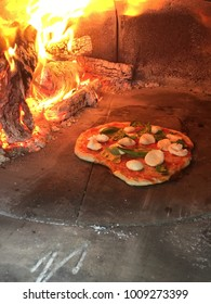 Pizza cooking in wood fire oven