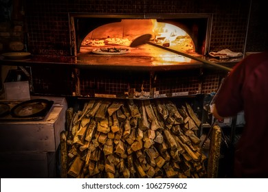 Pizza cooking in a wood fired pizza oven with plenty of fuel underneath.