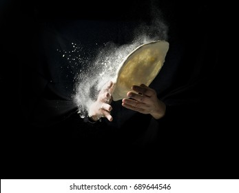 pizza cook's hand with dough and flour
