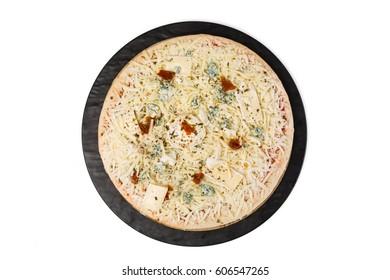 Pizza cruda sobre plato negro y fondo blanco