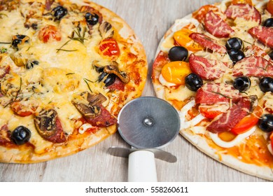 Pizza cutter together with two large pizzas with cheese olives and salami, mushrooms and tomatoes. On a wooden stand.