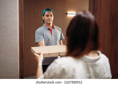 Pizza delivery boy gives box to female customer