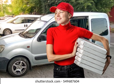 Pizza delivery girl holding boxes with pizza near car on a sunny summer day