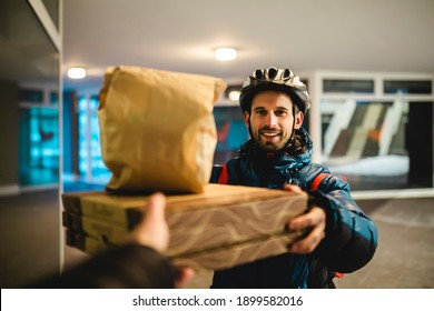 Pizza delivery home. The courier with the bicycle helmet delivers the hot food. Takeaway pizza, food delivery.