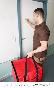 Pizza Delivery Man Knocking The Door With A Large Red Bag In His Hand