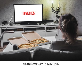 Pizza in delivey box with TV series in living room.