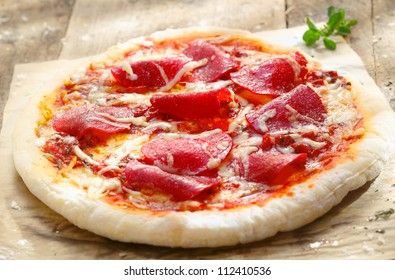 Pizza Diavolo with Salami meat and red hot chili peppers on a rustic table in a pizza parlor, for italian cuisine concept