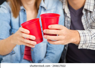 Pizza dinner. Closeup hands of friends toasting with red plastic cups