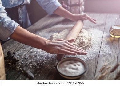Pizza dough with ingredients on rustic wooden table. Woman hands keep rolling pin with flour on dark brown table, baking background, menu, recipe. Preparing bread dough on wooden table in a bakery.