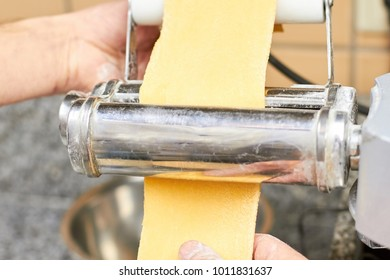 Pizza dough roller mixer in action. Working pizza dough machine equipment.