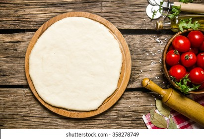 Pizza dough with tomatoes, and herbs with a rolling pin. On wooden background. Top view