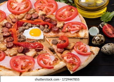 pizza with egg, ham, meat and tomatoes on wooden background.