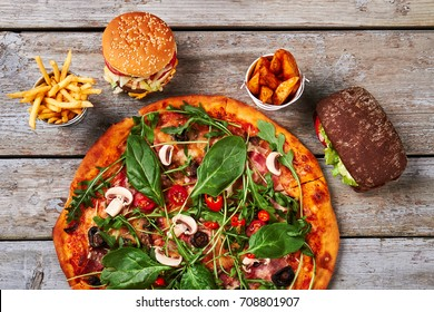 Pizza, fast food close up. Fried potatoes, burgers, baked pizza. Snack in restaurant.