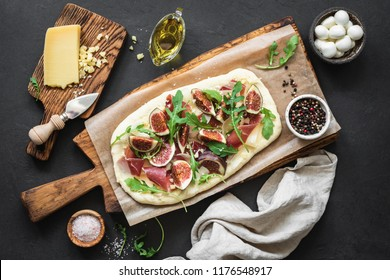 Pizza flatbread with figs, prosciutto, arugula and cheese on wooden serving board over black concrete background. Top view. Tasty homemade pizza