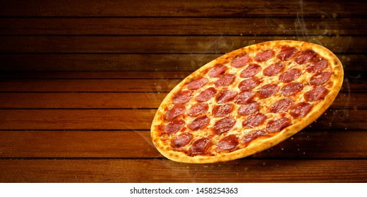Pizza in flying on wooden table desk background. Concept promotional flyer and poster for Restaurants or pizzerias, template with hot delicious pepperoni pizza closeup with steam smoke, tasty