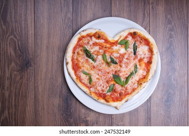 Pizza in the form of heart on a wooden background