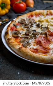 Pizza four seasons on dark concrete background