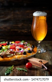 Pizza and glass of beer on a wooden table