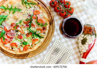 Pizza with glass of wineand sprig of tomatoes