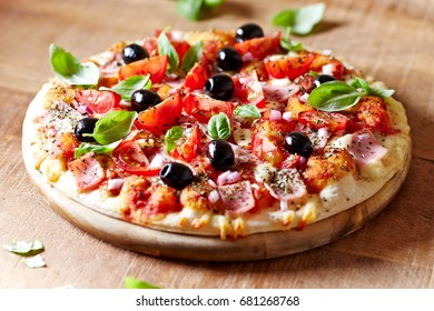 Pizza with ham, black olives, cherry tomatoes, spices and fresh basil. Italian pizza. Home made food. Concept for a tasty and hearty meal. Brown wooden background.