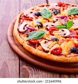 Pizza with ham, pepper, mushrooms and olives. Delicious fresh pizza served on wooden table. Pizza with tomato, salami and olives