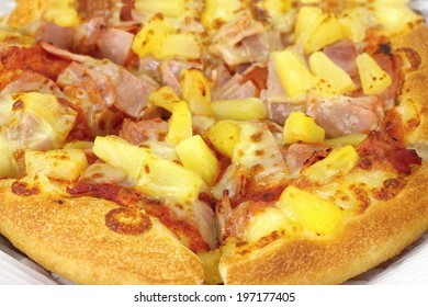 Pizza with Hawaiian pineapple and ham, topped with cheese