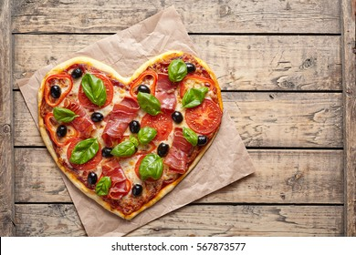 Pizza heart love Valentine's Day symbol romantic dinner Italian food. Prosciutto, olives, tomatoes, parsley, basil and mozzarella cheese meal served on vintage wooden table
