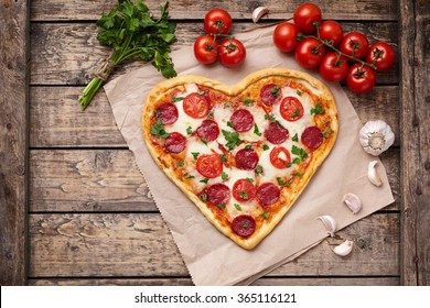 Pizza heart shaped with pepperoni, tomatoes, mozzarella, garlic and parsley on vintage wooden table background. Concept of romantic love for Valentines Day.