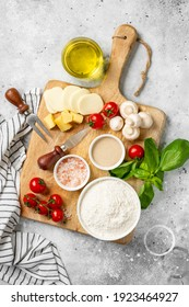 Pizza ingredients on a culinary background. Flour, yeast, salt, water, olive oil, parmesan, cheese, mozzarella, basil, tomatoes on the table. The concept of preparing for baking pizza or pie. Top view