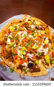 Pizza made of toasted corn taco tortilla with meat, tomato, onion, cream and sauces, Mexican style.