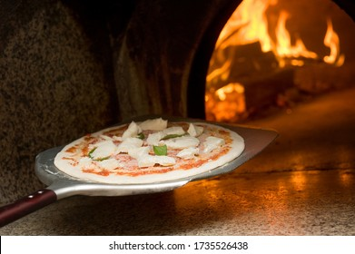 the pizza maker bake a real margherita pizza in the wood oven with the shovel