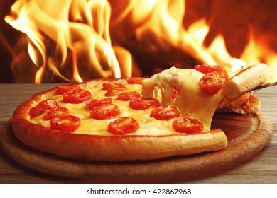 Pizza Margarita and removed slice on fire flame background