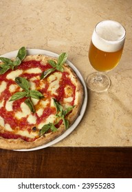 """Pizza """"margherita"""" with a fresh glass of beer"""