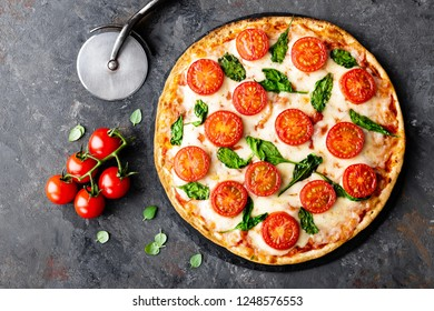 Pizza Margherita with mozzarella cheese, basil  and tomatoes Traditional italian food. Classic recipe. Top view