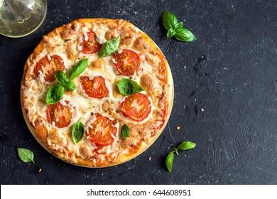 披薩瑪格麗特黑色石頭背景,上視圖。 比薩瑪格麗塔配西紅柿,羅勒和馬蘇里拉奶酪。