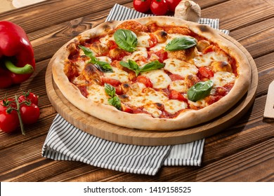 Pizza Margherita on wooden background, top view. Flyer and poster for Restaurants or pizzerias, template with delicious taste margarita pizza, mozzarella cheese, cherry tomatoes.