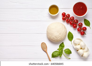 Pizza margherita traditional preparation recipe with baking ingridients: raw dough, cherry tomatoes, basil, tomato sauce and olive oil on white kitchen table background