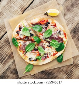 Pizza with meat, pepper, olives, onion and spinach on a wooden table, top view with a copy space
