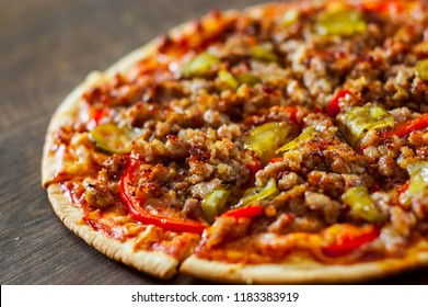 Pizza with Mozzarella cheese, minced meat and vegetables. Italian pizza on wooden background.