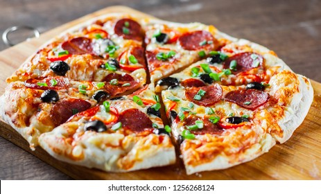 Pizza with Mozzarella cheese, pepperoni, tomato, pepper, olive, salami. Italian pizza on wooden table background