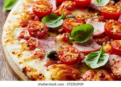 Pizza with Mozzarella, Ham, halved Cherry Tomatoes, Capers, Spices and Fresh Basil. Italian pizza. Home made food. Concept for a tasty and hearty meal. Close up.
