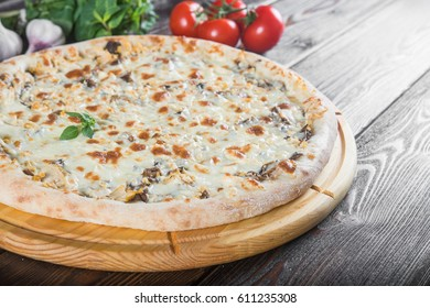 Pizza with mushrooms and chicken. Macro. Creative author's pizza. This is a series of different pizzas. The main types of pizza are photographed from one angle.