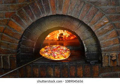 Pizza near the stone stove with fire. Background of a traditional pizzeria restaurant with a fire place.