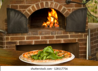 Pizza on a plate with pizza oven in background