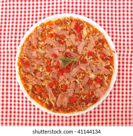 Pizza on white plate and red tablecloth
